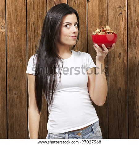 woman holding a delicious red breakfast bowl against a wooden background