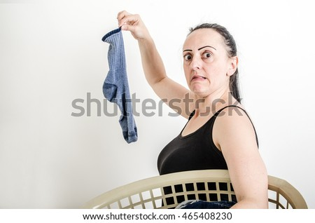 Woman holding a dirty, smelly sock out of washing basket with a disgusted look on her face.
