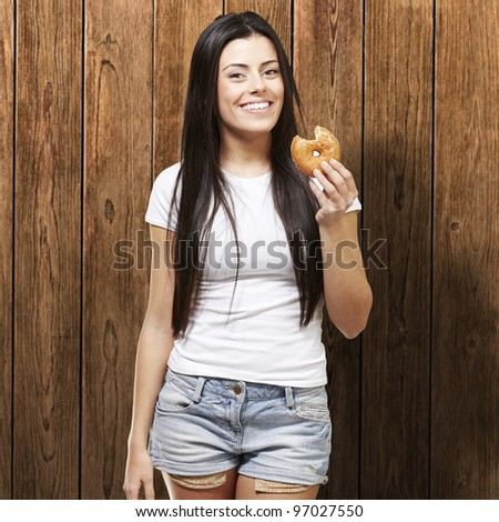 woman holding a donut with a bite against a wooden background