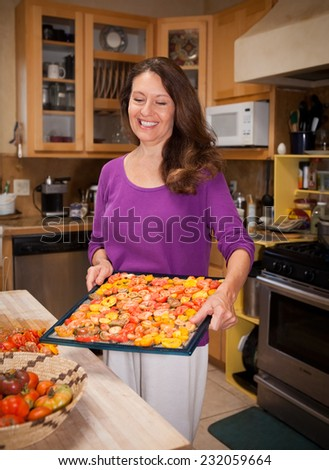 Woman holding a dryer rack full of heirloom tomatoes - stock photo