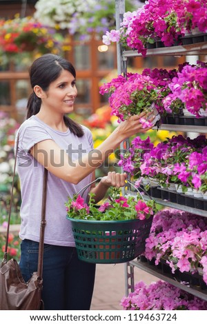 Woman holding a flower and a basket in garden centre - stock photo