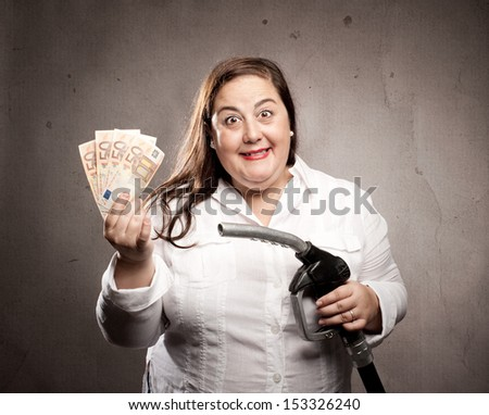 woman holding a fuel pump nozzle - stock photo