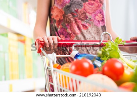 Woman holding a full cart at supermarket with fresh vegetables. - stock photo