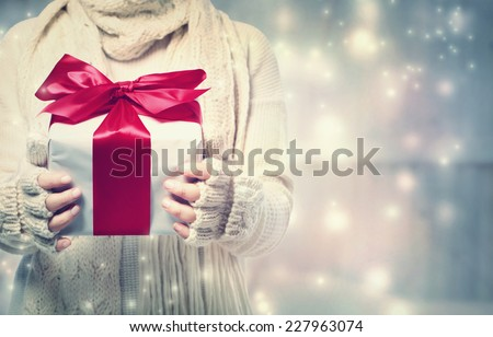 Woman holding a giftbox with red ribbon in the snowy night - stock photo