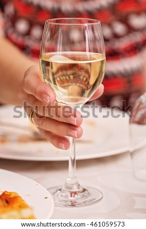 Woman holding a glass of white wine during lunch