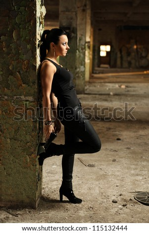 woman holding a gun leaning against column - stock photo