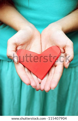 woman holding a heart out of paper - stock photo