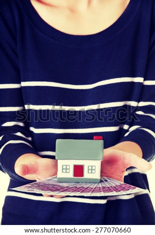 Woman holding a house model and euro bills. - stock photo
