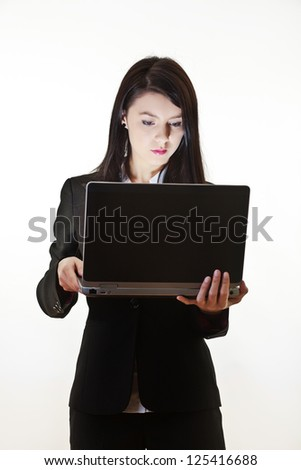 woman holding a laptop computer looking at the screen where there is a light source coming from it - stock photo
