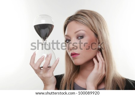 woman holding a large glass sand timer in her hands watching time run out - stock photo