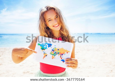 woman holding a map with travel destinations - stock photo