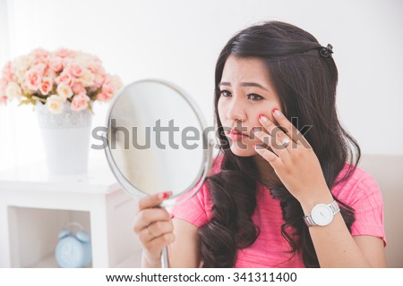Woman holding a mirror, touch and worrying about her face - stock photo