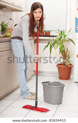 Woman holding a mop and cleaning kitchen floor
