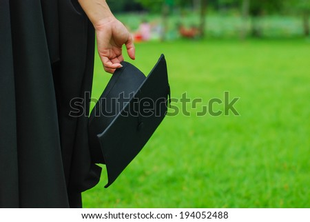 woman holding a mortar board in focus - stock photo