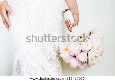 Woman Holding a nice Wedding Bouquet in front of a white Wall