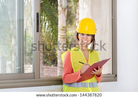 Woman holding a notepad and writing at work in a construction - stock photo