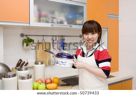 woman holding a pan in kitchen - stock photo