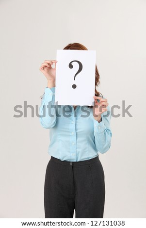 woman holding a paper printed a big question markcovered her face