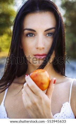Woman holding a peach, day, outdoor. Brunette female showing a fruit. Middle-age woman in underwear, on the background of nature background