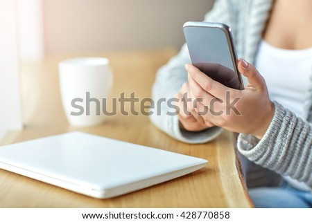 Woman holding a phone in hands and writes the message at the cafe. Close up