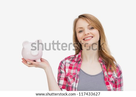 Woman holding a piggy bank while looking at camera against a white background