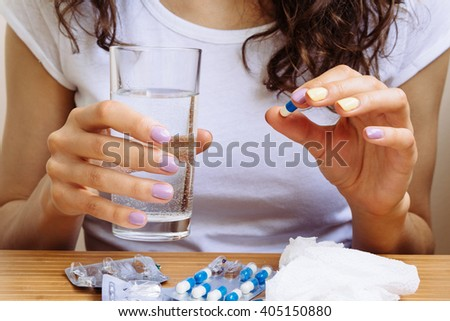 Woman holding a pill and a glass of water in hands