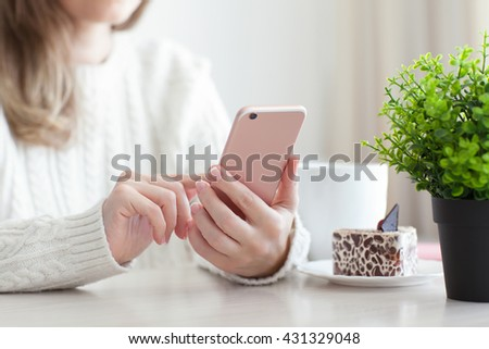 Woman holding a pink mobile phone in a cafe