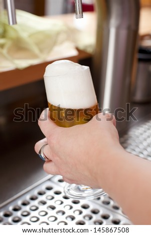 Woman holding a pint glass of draft beer with a very frothy head when dispensing it behind a bar counter - stock photo
