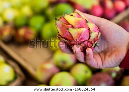 Woman holding a Pithaya (Red Dragon Fruit) in the fruit section of a grocery store