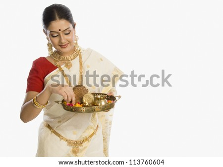 Woman holding a plate of religious offerings - stock photo