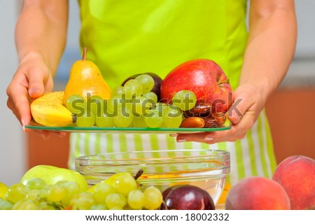woman holding a plate with fruits
