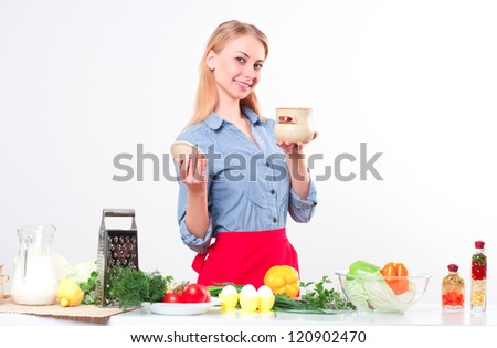 woman holding a pot for cooking, smiling and looking into the camera - stock photo