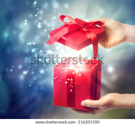 Woman holding a red gift box on a blue holiday lights background - stock photo