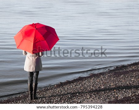 Woman holding a red umbrella walking on a rainy day at a beach.