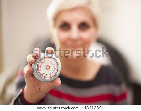 Woman holding a retro timer alarm. Time management concept. Selective focus.  - stock photo