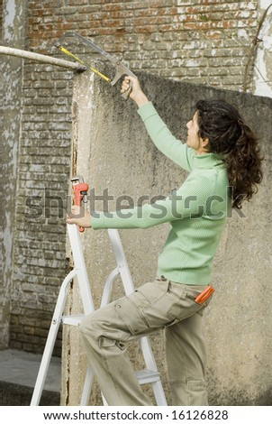 Woman holding a saw and standing on a ladder. Vertically framed photo.