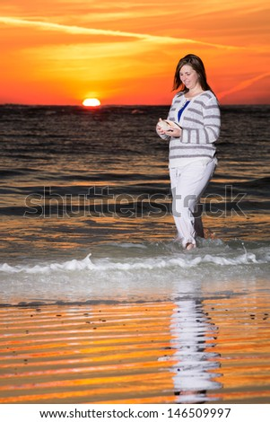Woman Holding a Shell on the Beach During Beautiful Sunset