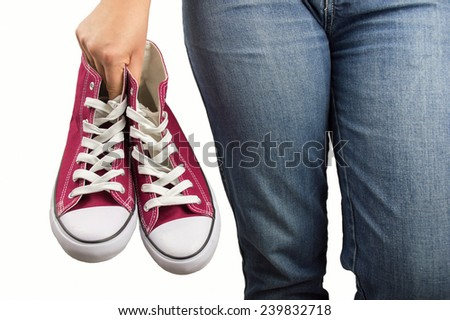 woman holding a shoe in hand and relaxed with white background - stock photo