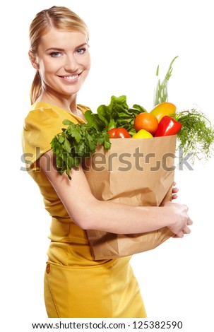 woman holding a shopping bag full of groceries, mango, salad,  radish, lemon, carrots on white background - stock photo