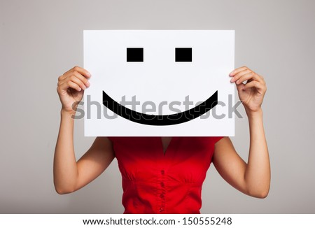 Woman holding a smiling face emoticon - stock photo