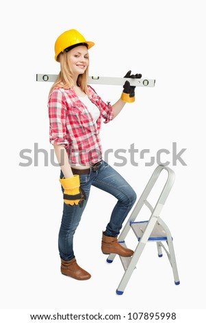 Woman holding a spirit level next to a step ladder against white background - stock photo