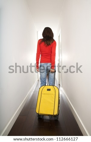woman holding a suitcase in white passage indoor