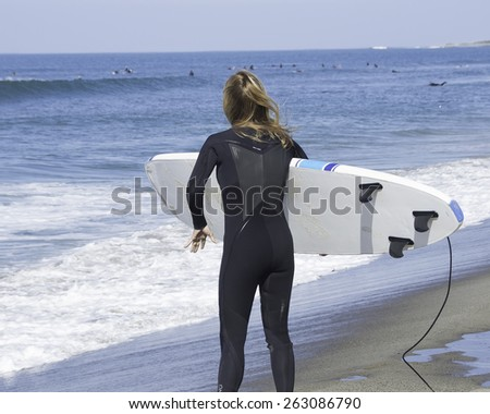 Woman holding a surfboard/Woman Surfer/Woman overlooking waves near the ocean - stock photo