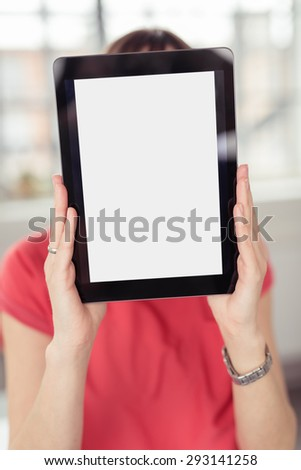 Woman holding a tablet-pc in front of her face with the blank white screen with copyspace facing the camera - stock photo