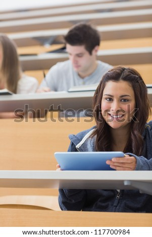 Woman holding a tablet pc while smiling and looking up in lecture hall - stock photo