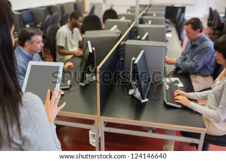 Woman holding a tablet pc while teaching her computer class - stock photo