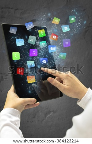 Woman holding a tablet with modern colorful floating apps and icons. Selective focus.