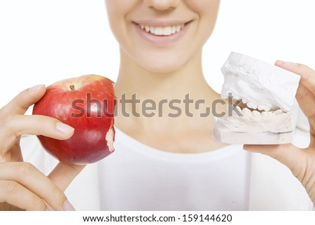 Woman holding a teeth sample and apple - stock photo
