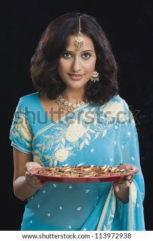 Woman holding a traditional Diwali thali and smiling