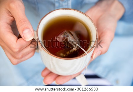 Woman Holding a Warm Cup of Freshly Brewed Tea - stock photo